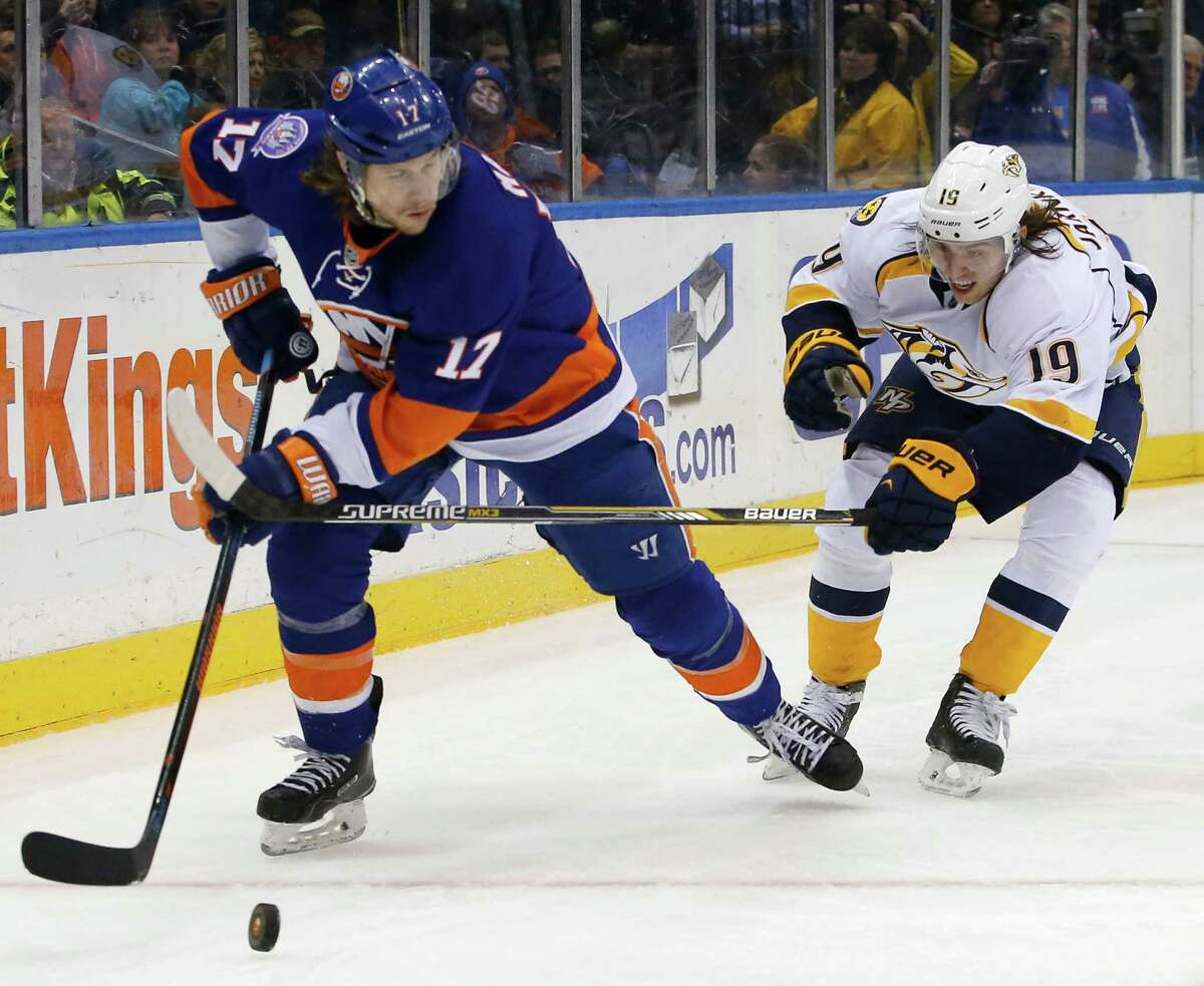 Nashville Predators center Calle Jarnkrok (19) of Sweden, defends New York Islanders left wing Matt Martin (17) in the second period of an NHL hockey game at Nassau Coliseum in Uniondale, N.Y., Thursday, Feb. 19, 2015. (AP Photo/Kathy Willens) ORG XMIT: UNI107
