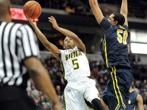 Siena's Evan Hymes, left, shoots for the hoop as Canisius' Josiah Heath defends during their basketball game on Thursday, Feb. 19, 2015, at Times Union Center in Albany, N.Y. (Cindy Schultz / Times Union) Photo: Cindy Schultz / 00030520B