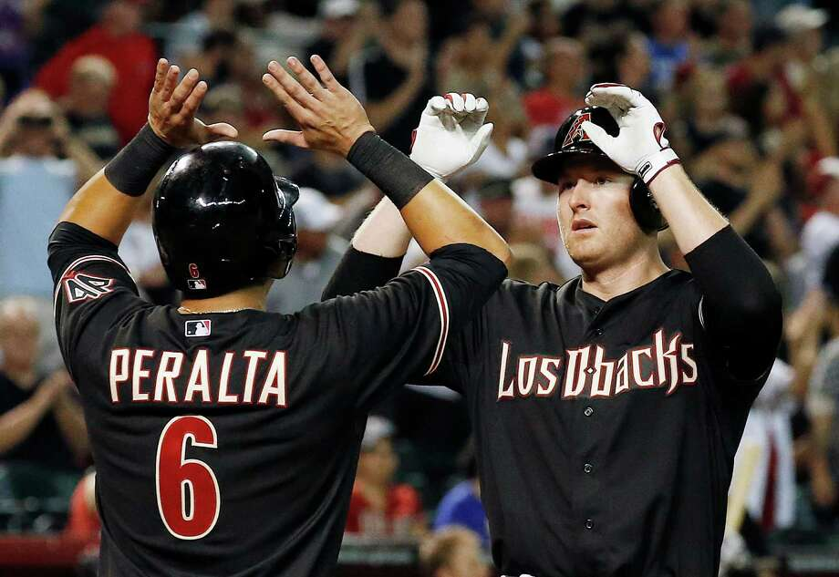 Diamondbacks outfielder Mark Trumbo (right) celebrates his three-run home run against the Cardinals with teammate David Peralta (6) back in in September in Phoenix. Trumbo has won his salary arbitration case against the Diamondbacks and will get a $6.9 million salary this year instead of the team's $5.3 million offer. Photo: Ross D. Franklin / Associated Press / AP