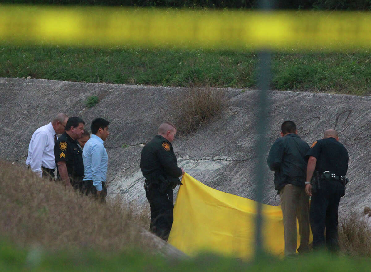 San Antonio police investigate the scene of a fatal shooting in a concrete culvert Friday February 20, 2015 on the 1100 block of Shadwell.