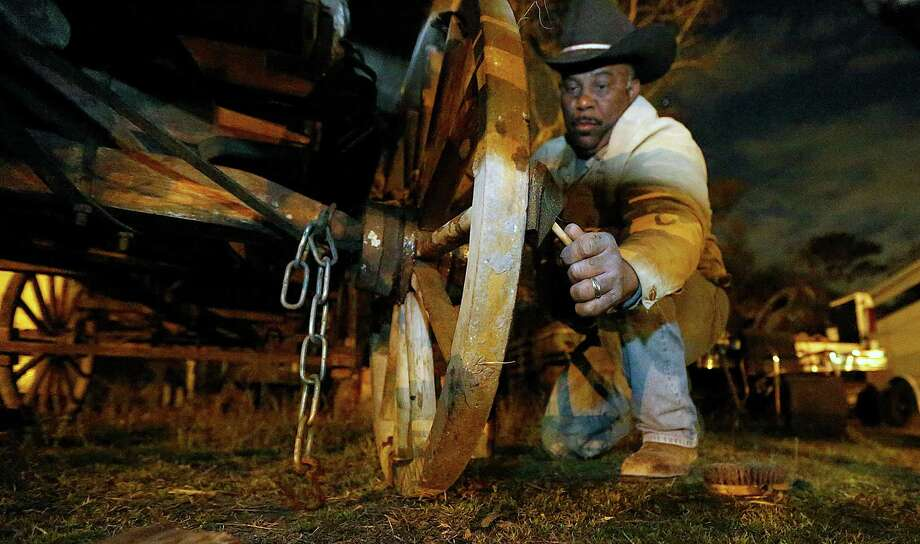 Northeast Trail Riders Association Trail Boss Anthony Bruno applies a wood sealer to a wagon at Bruno's Triangle 7 Arena. Photo: James Nielsen, Houston Chronicle / © 2015  Houston Chronicle