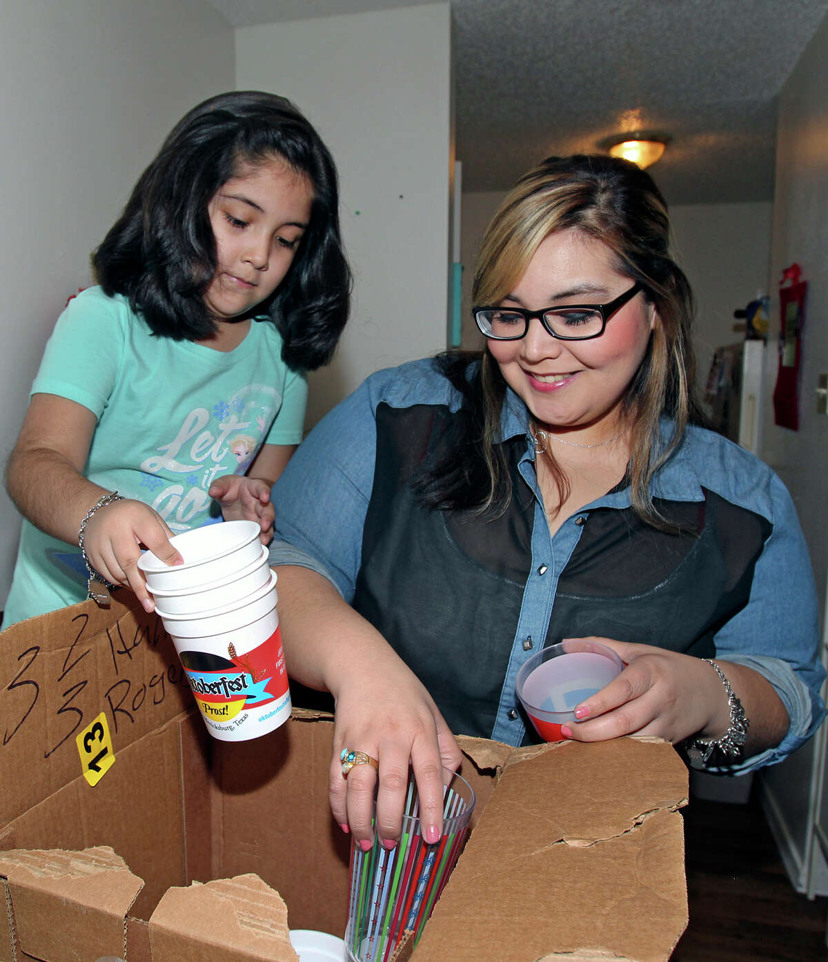 Elizabeth Rodriguez and her daughter, 8-year-old Jaydlyn Garza, pack kitchen items as they she prepare to move out of their apartment and into a home they are buying later this month.