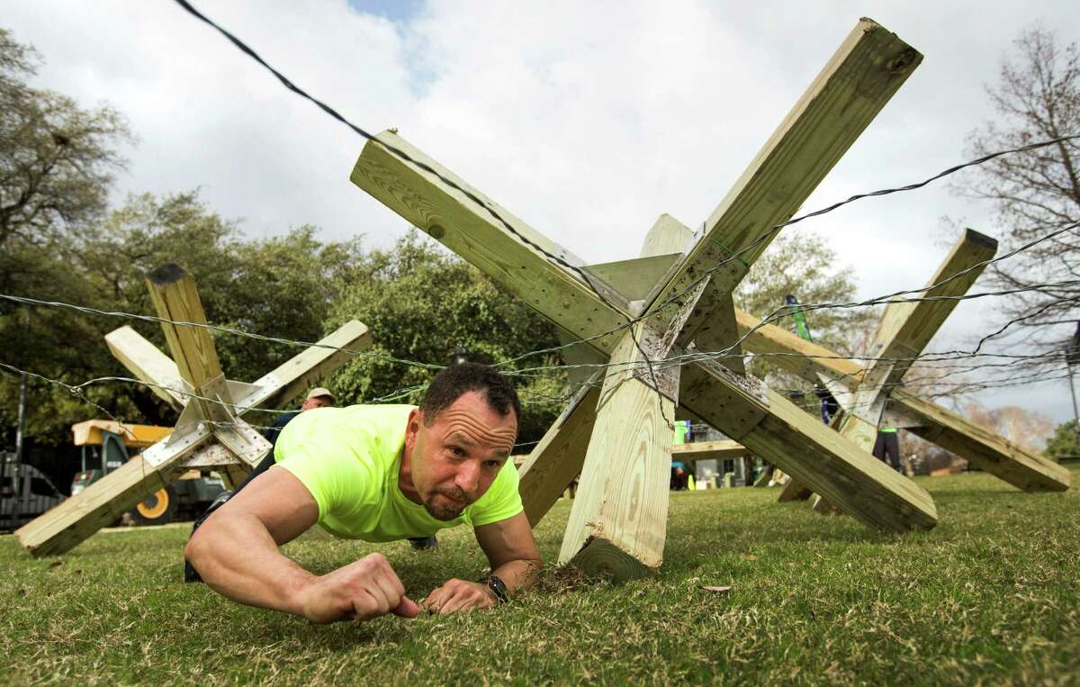 Juan Osuna, of Willis, crawls under an obstacle during a demonstration of the upcoming BattleFrog obstacle course race at Sam Houston Park on Friday, Feb. 20, 2015, in Houston. BattleFrog, a race course of three different distances, designed by former Navy SEALs, is scheduled for March 28 and 29 at Rio Bravo MX Park in Houston, the series' first stop in Texas.
