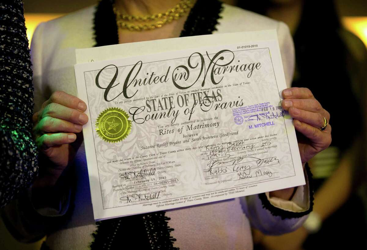 Suzanne Bryant shows her marriage license at Highland Lounge in Austin, Texas, on Thursday, Feb. 19, 2015, after she and her partner, Sarah Goodfriend, became the first legally married gay couple in Texas. (AP Photo/Austin American-Statesman, Jay Janner)
