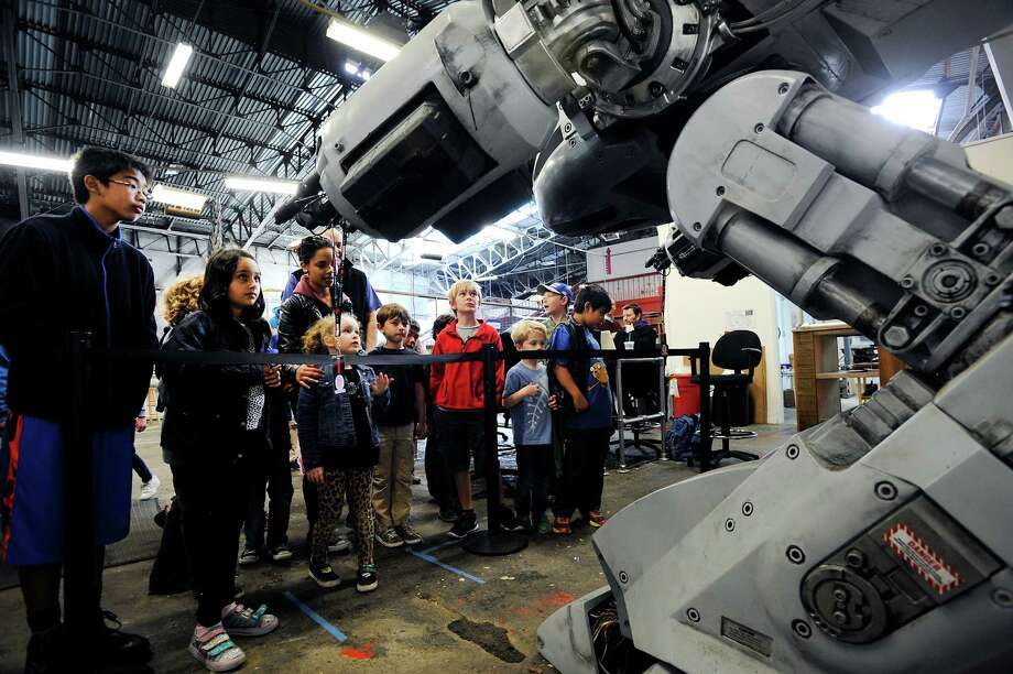 """Students from the Presidio YMCA check out a life-size replica of the ED-209 robot from the movie """"Robocop"""" in the Maker area during a preview of the centennial celebration of the 1915 Panama Pacific Fair at the Palace of Fine Arts in San Francisco. Photo: Michael Short / Special To The Chronicle / ONLINE_YES"""