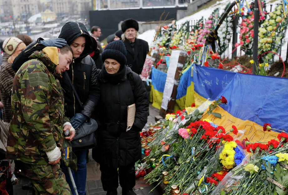 People in Kiev, Ukraine, pay respects to those who died during antigovernment protests in 2013-14. Photo: Sergei Chuzavkov / Associated Press / AP