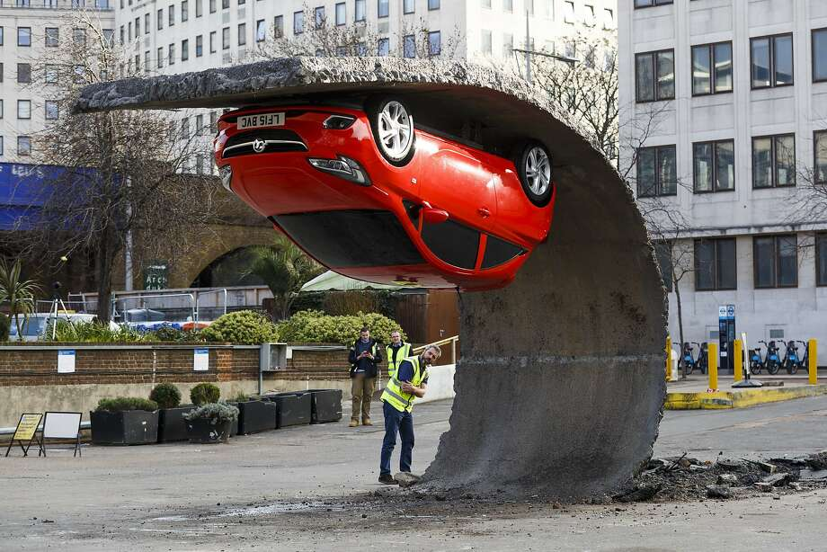 PEELING OUT IN THE PARKING LOT:Asphalt appears to have folded back from the surface of a London lot in this installation by artist Alex Chinneck. The gravity-defying car is a Vauxhall Corsa. The illusionary artwork, which uses hidden engineering and complex manipulation of concealed steel, was commissioned by Vauxhall. Photo: Tristan Fewings, Getty Images For Vauxhall Motors