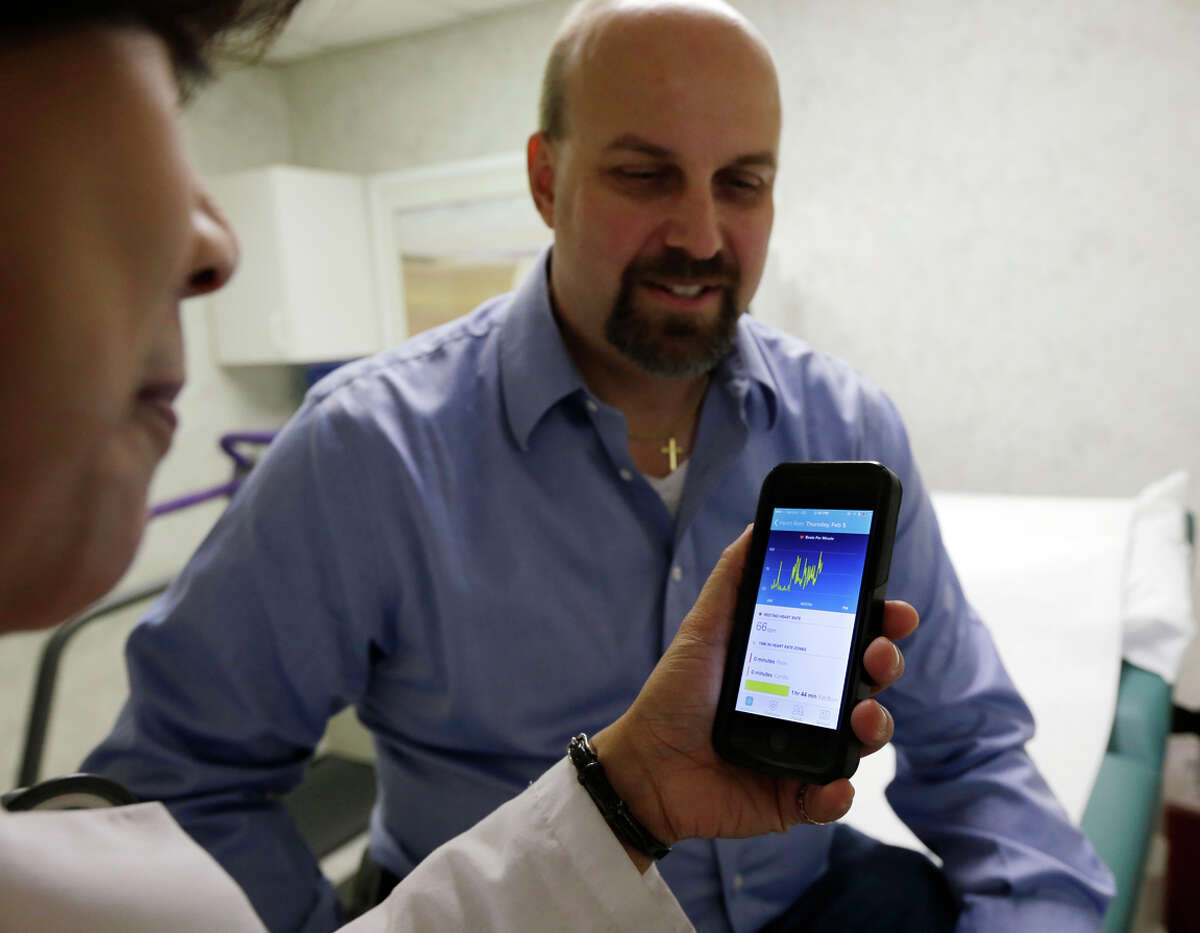 Hackensack University Medical Center cardiologist Dr. Sarah Timmapuri checks a smartphone that records data from patient Gary Wilhelm's Fitbit.