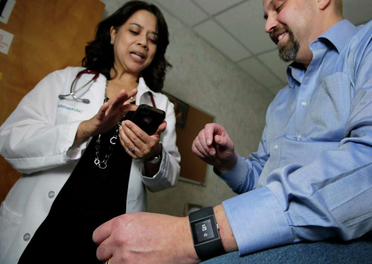 In this Thursday, Feb. 5, 2015 photograph, Hackensack University Medical Center cardiologist Dr. Sarah Timmapuri, left, looks at data on a smart phone that is synchronized to a new Fitbit Surge that is on the wrist of patient Gary Wilhelm, 51, during an examination in Hackensack, N.J. Wilhelm, who works at Hackensack University Medical Center on payroll and finance technology, joined Hackensack's app test after he suffered a heart attack in October. (AP Photo/Mel Evans)