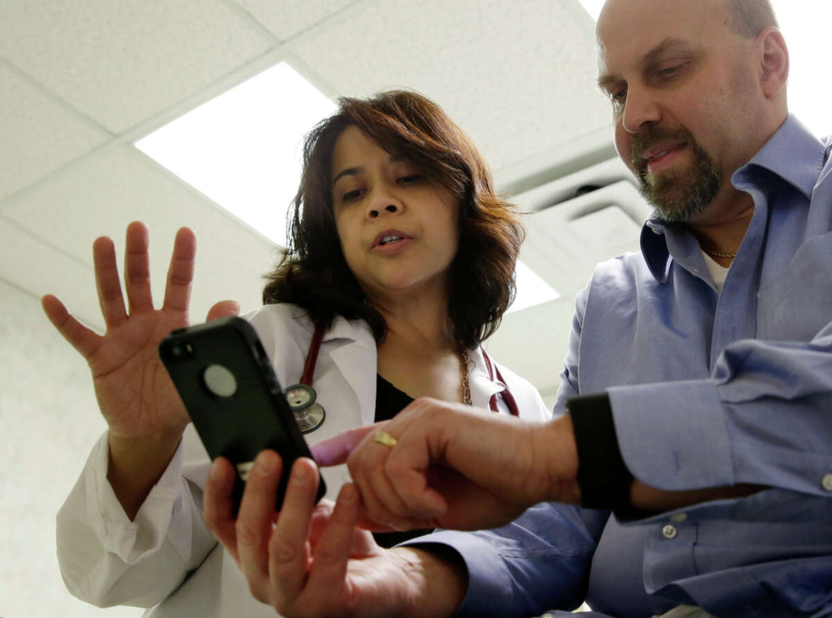 Dr. Sarah Timmapuri looks at data synchronized to a Fitbit Surge worn by heart patient Gary Wilhelm.
