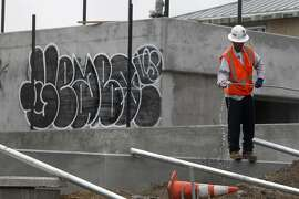 A man works near a graffitied wall on the site of new construction at Dolores Park in the Mission District of San Francisco, Calif. Friday, February 20, 2015 after vandals caused $100,00 in damage over the weekend, setting back the date for re-opening indefinitely.
