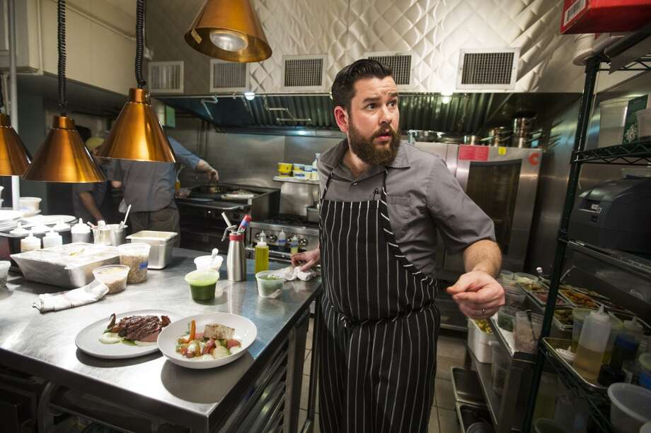 Chef Adam Dorris checks on an order as he prepares a pair of dishes at Pax Americana on Friday, Dec. 26, 2014, in Houston. ( Brett Coomer / Houston Chronicle ) Photo: Brett Coomer, Houston Chronicle