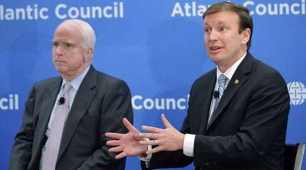 US Senator Christopher Murphy (R), D-CT, speaks as US Senator John McCain, R-AZ,  watches during the Toward a Europe Whole and Free conference at the Atlantic Council on April 29, 2014 in Washington, DC.