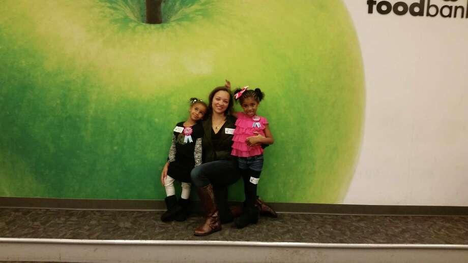 Eden Bashir, from left, Allison Odom-Bashir and Jasmine Bashir at the Houston Food Bank for the girls' joint birthday celebration.