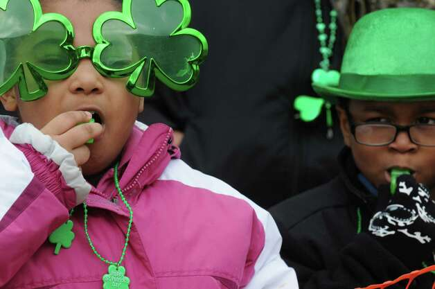Eight-year-old Javianna McCall, left, and Irvin Vasquez, 7-years-old, blow green whistles as they watch the 64th Annual Albany St Patrick's Day Parade on Saturday March 15, 2014 in Albany, N.Y. (Michael P. Farrell/Times Union) Photo: Michael P. Farrell / 00025878A
