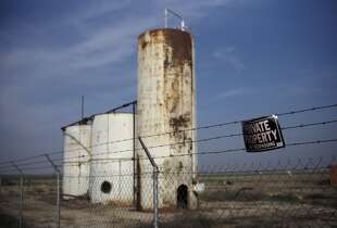 California: A private property sign hangs on the fence of a shut down injection well located next to an almond orchard owned by Palla Farms, Thursday, Jan. 15, 2015, in Bakersfield, Calif. Palla Farms filed suite blaming several oil companies for contaminating the local groundwater and killing cherry trees.