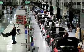 A worker carries a front-end part along the assembly at Tesla Motors.