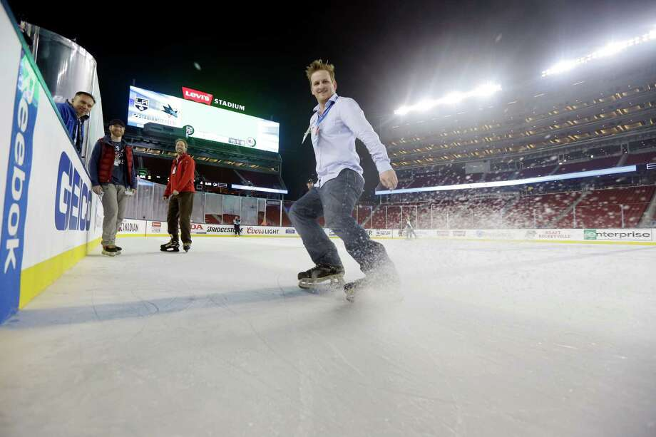 Television producer Scott Moring tests the ice at Levi's Stadium during a media session leading up to Saturday's game. Photo: Marcio Jose Sanchez / Associated Press / AP