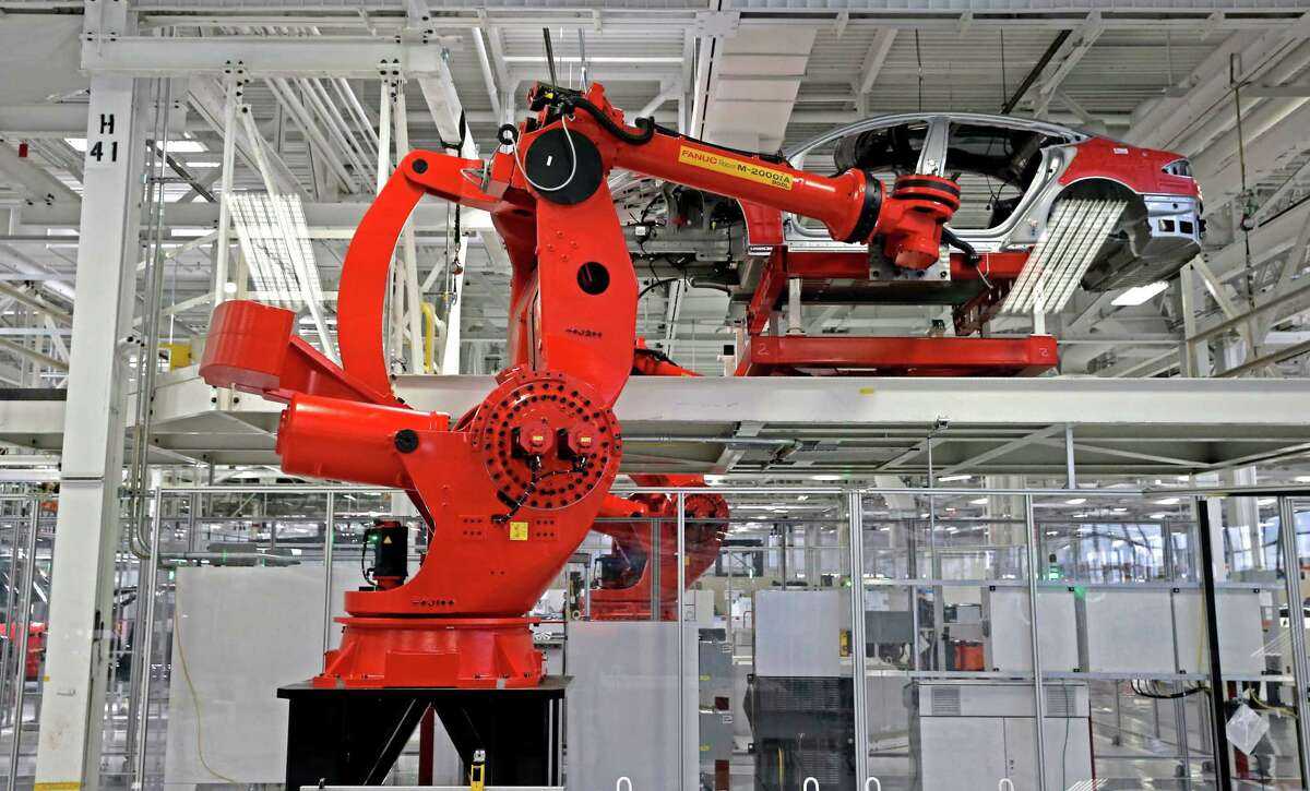 Giant robot arms pick up and move cars along the assembly line at Tesla Motors.