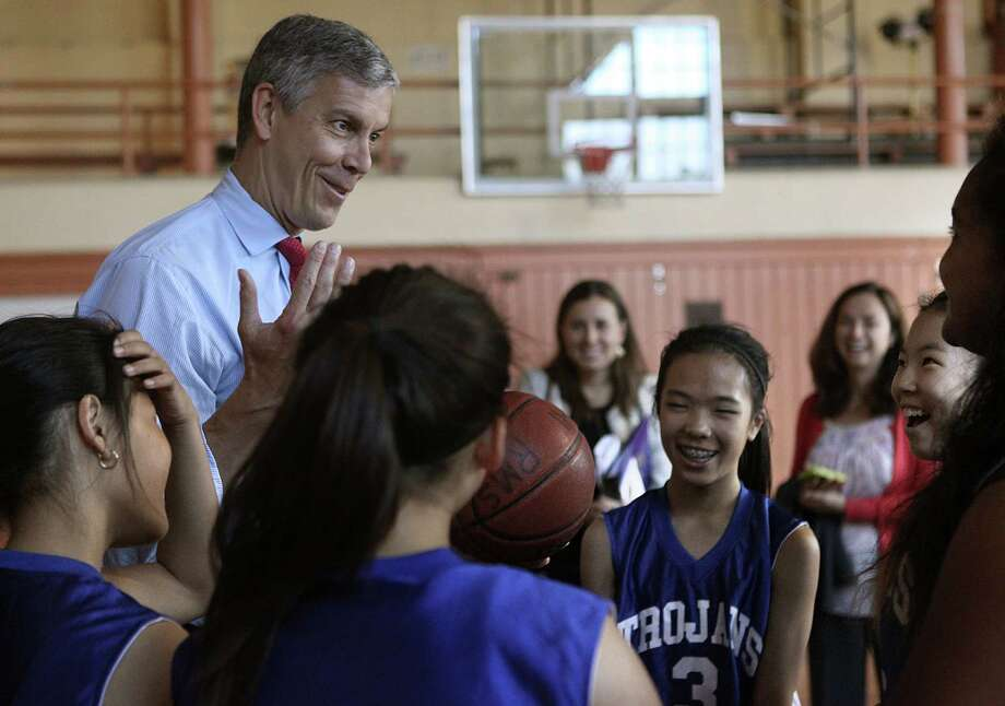 U.S. Secretary of Education Arne Duncan (top left) and the Trojans basketball team exchange signed basketballs in the gym of Roosevelt Middle School in San Francisco in October. Photo: Liz Hafalia / The Chronicle / ONLINE_YES