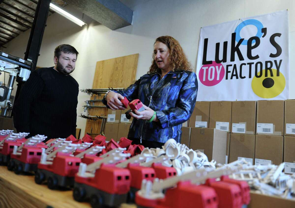 U.S. Rep. Elizabeth Esty takes a look at toy trucks with toy designer Luke Barber at Luke's Toy Factory in Danbury, Conn. Friday, Feb. 20, 2015. Rep. Esty toured the factory to talk to its owners and look at the products, paint-free toys from a plastic-wood composite using sawdust from U.S. furniture makers.