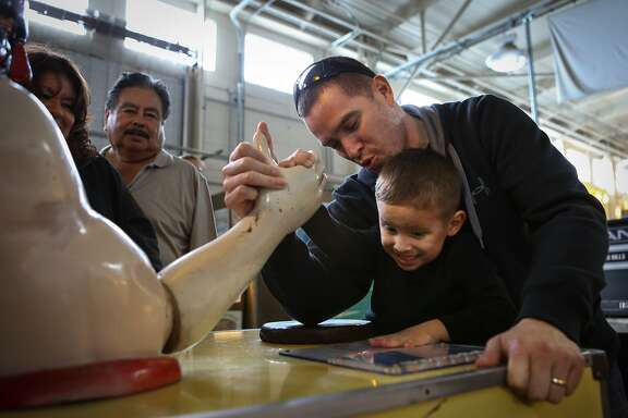 Kingston Henriquez, 3, gets some help from his dad, Rommel Henriquez, in beating the mechanical arm wrestler at the Musee Mecanique located in Fisherman's Warf, San Francisco on Tuesday, February 17, 2015.