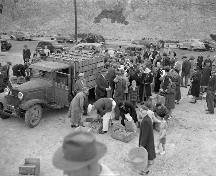 A crowd gathers around potato farmers at the farmers' market at Market Street and Duboce Avenue in March 1944, less than a year after it opened. Photo: Chronicle File / The Chronicle / ONLINE_YES