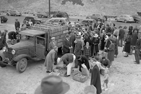 A crowd gathers around potato farmers at the farmers' market at Market Street and Duboce Avenue in March 1944, less than a year after it opened.