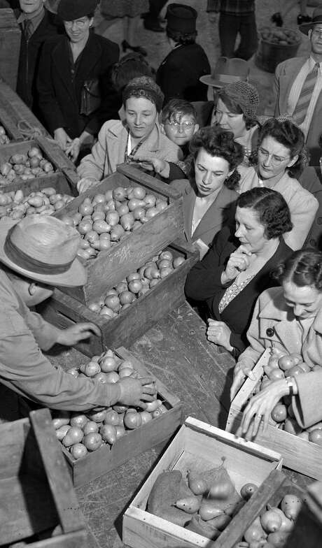 Customers inspect pears in March 1944 during the second year of operation of the San Francisco farmers' market at Market Street and Duboce Avenue. Photo: Chronicle File / The Chronicle / ONLINE_YES