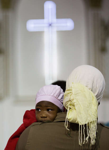 An African Christian mother and her child attend Mass at Anglican church in Tripoli, Libya. Numbers at the church have dropped since fighting in the capital last summer forced many expatriate workers to leave. Violence continued in Libya on Friday. Photo: Mohamed Ben Khalifa, STR / AP