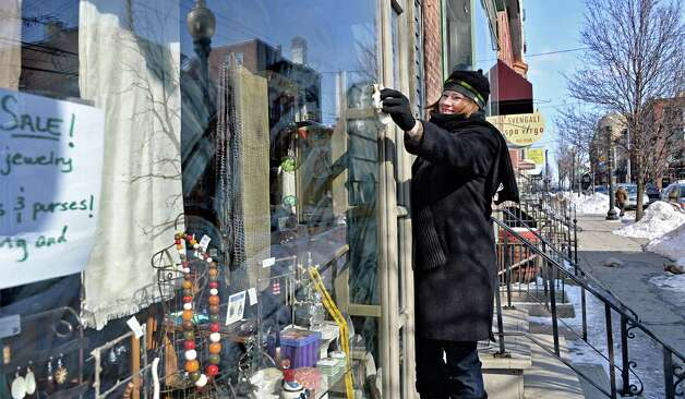 Jewelry designer Elissa Halloran struggles against the cold to wash the windows of her Lark Street shop Friday, Feb. 20, 2015, in Albany, NY.  (John Carl D'Annibale / Times Union) Photo: John Carl D'Annibale / 00030704A