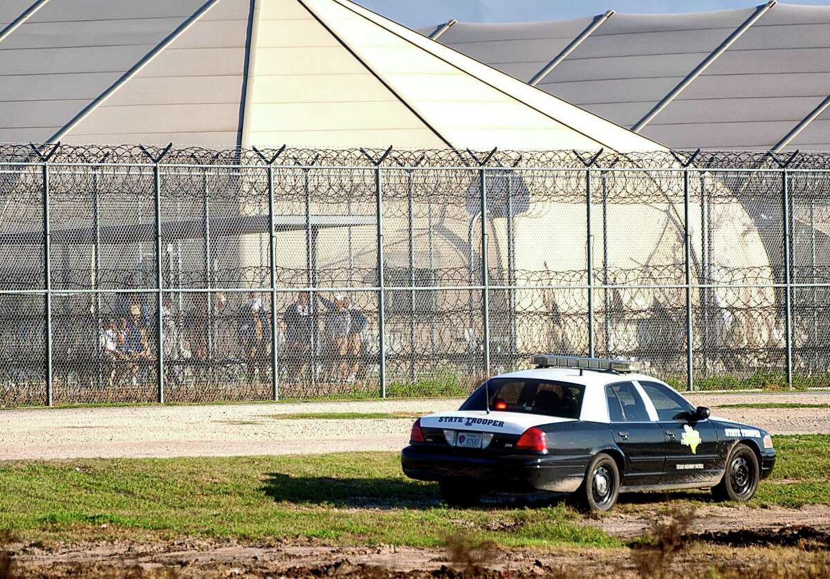 Prisoners stand at the western fence as law enforcement officials from a wide variety of agencies converge on the Willacy County Correctional Center in Raymondville, Texas on Friday, Feb. 20, 2015 in response to a prisoner uprising at the private immigration detention center. A statement from prison owner Management and Training Corp. said several inmates refused to participate in regular work duties early Friday. Inmates told center officials of their dissatisfaction with medical services. (AP Photo/Valley Morning Star, David Pike)