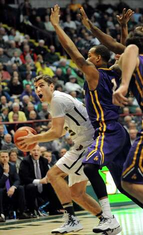 Siena's Rob Poole, left, holds off UAlbany's defense during their basketball game on Saturday Dec. 13, 2014, at Times Union Center in Albany, N.Y. (Cindy Schultz / Times Union) Photo: Cindy Schultz / 00029816A