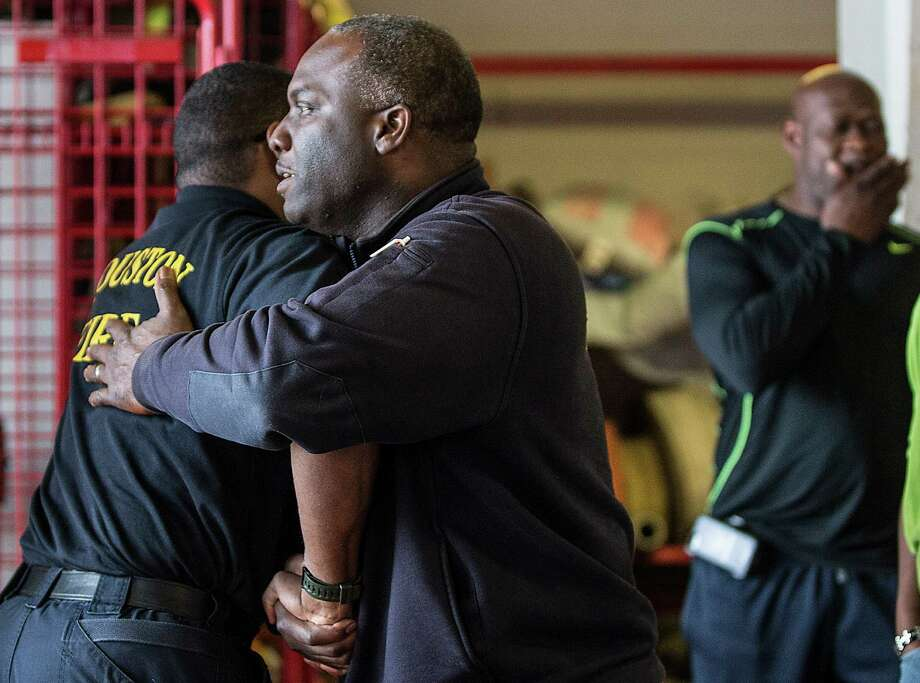 Capt. Mundo Olford, center, embraces Capt. Eugene Thomas at HFD Station 46 after a news conference Friday on the condition of Capt. Dwight Bazile, who collapsed at the scene of a house fire Thursday.  Photo: Brett Coomer, Staff / © 2015 Houston Chronicle