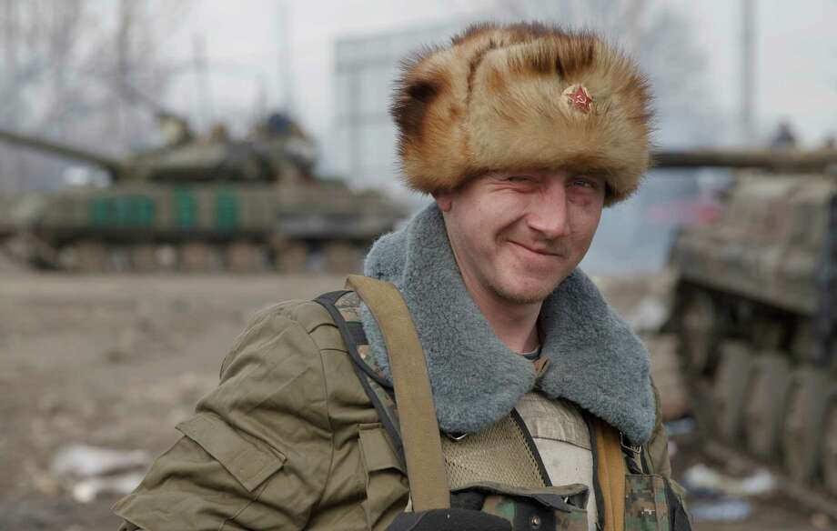 A Russia-backed rebel winks an eye in Debaltseve, Ukraine, Friday, Feb. 20, 2015. After weeks of relentless fighting, the embattled Ukrainian rail hub of Debaltseve fell Wednesday to Russia-backed separatists, who hoisted a flag in triumph over the town. The Ukrainian president confirmed that he had ordered troops to pull out and the rebels reported taking hundreds of soldiers captive.(AP Photo/Vadim Ghirda) Photo: Vadim Ghirda, STF / AP
