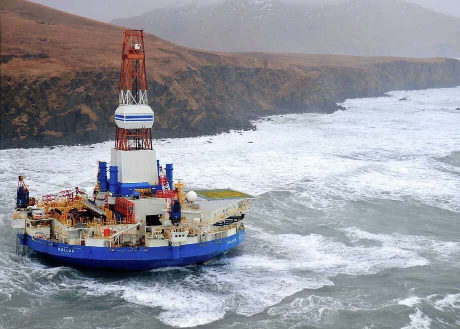 """Shell's mobile drilling unit, Kulluk, is shown after it had run aground. The National Transportation Safety Board reviewed the five-day fight to control the Kulluk and concluded that Shell had made """"inadequate assessment of the risk"""" of towing it across stormy seas. Photo: New York Times File Photo / U.S. COAST GUARD"""