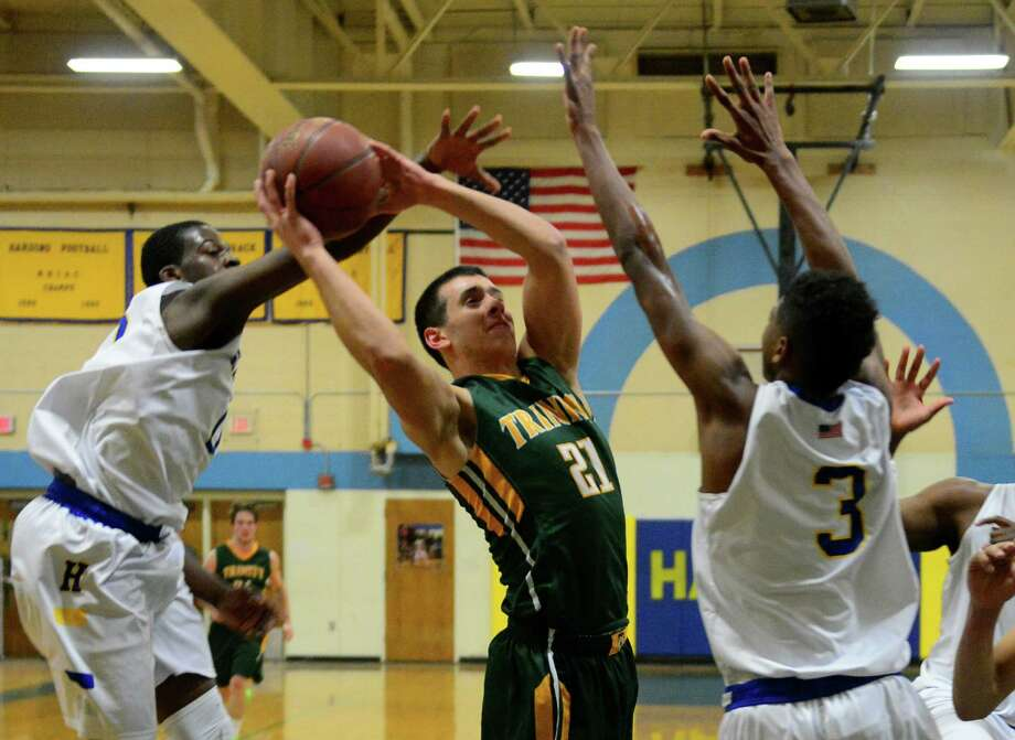 Harding's Anthony Gadsden, left, reaches in to disrupt a shot attempt by Trinity Catholic's Anthony Lombardi, during boys basketball action in Bridgeport, Conn. on Friday Feb. 20, 2015. Defending at right is Harding's Taisun Phommachanh. Photo: Christian Abraham / Connecticut Post