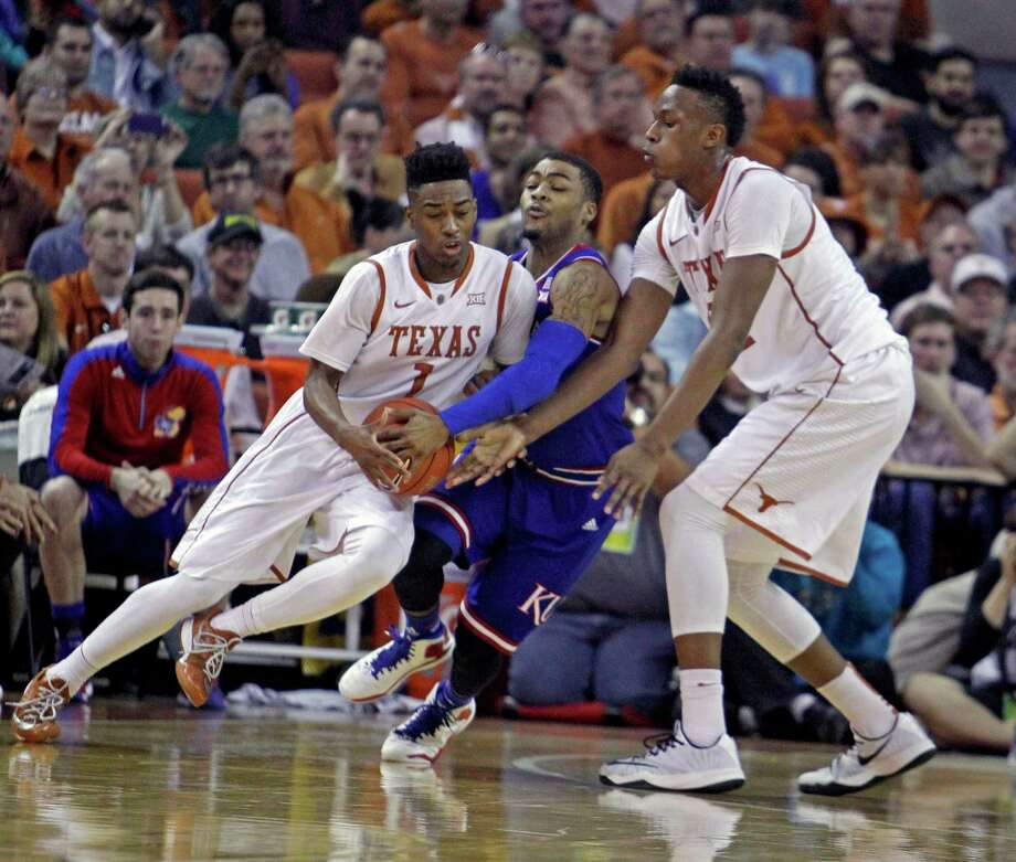 Texas guard Isaiah Taylor, left, drives around Kansas' Frank Mason III, center, as Texas forward Myles Turner, right, lends a hand. Taylor and Turner are considered NBA material, but their immediate goal is the NCAA Tournament. Photo: Michael Thomas, FRE / FR65778 AP