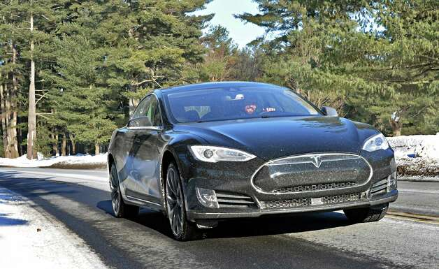 Tesla owner advisor Patrick  Moriarty drives a new Tesla Model S P85D along the Avenue of the Pines in Saratoga Spa State Park Friday, Feb. 20, 2015, in Saratoga Springs, NY.  (John Carl D'Annibale / Times Union) Photo: John Carl D'Annibale / 00030693A