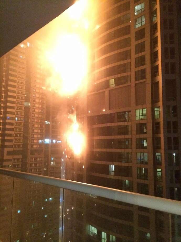 This photo provided by Rhea Saran shows flames coming from a high rise tower in Dubai's marina district Saturday, Feb. 21, 2015. The fire broke out early Saturday in the Torch tower on the northeastern end of the densely populated district, which is packed with multi-story skyscrapers. Debris from the fire cluttered nearby streets after the blaze appeared to be extinguished. (AP Photo/Rhea Saran) Photo: Rhea Saran, Associated Press