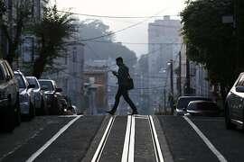 A man crosses Washington Street in San Francisco's Nob Hill neighborhood on Thursday, Feb. 19, 2015.