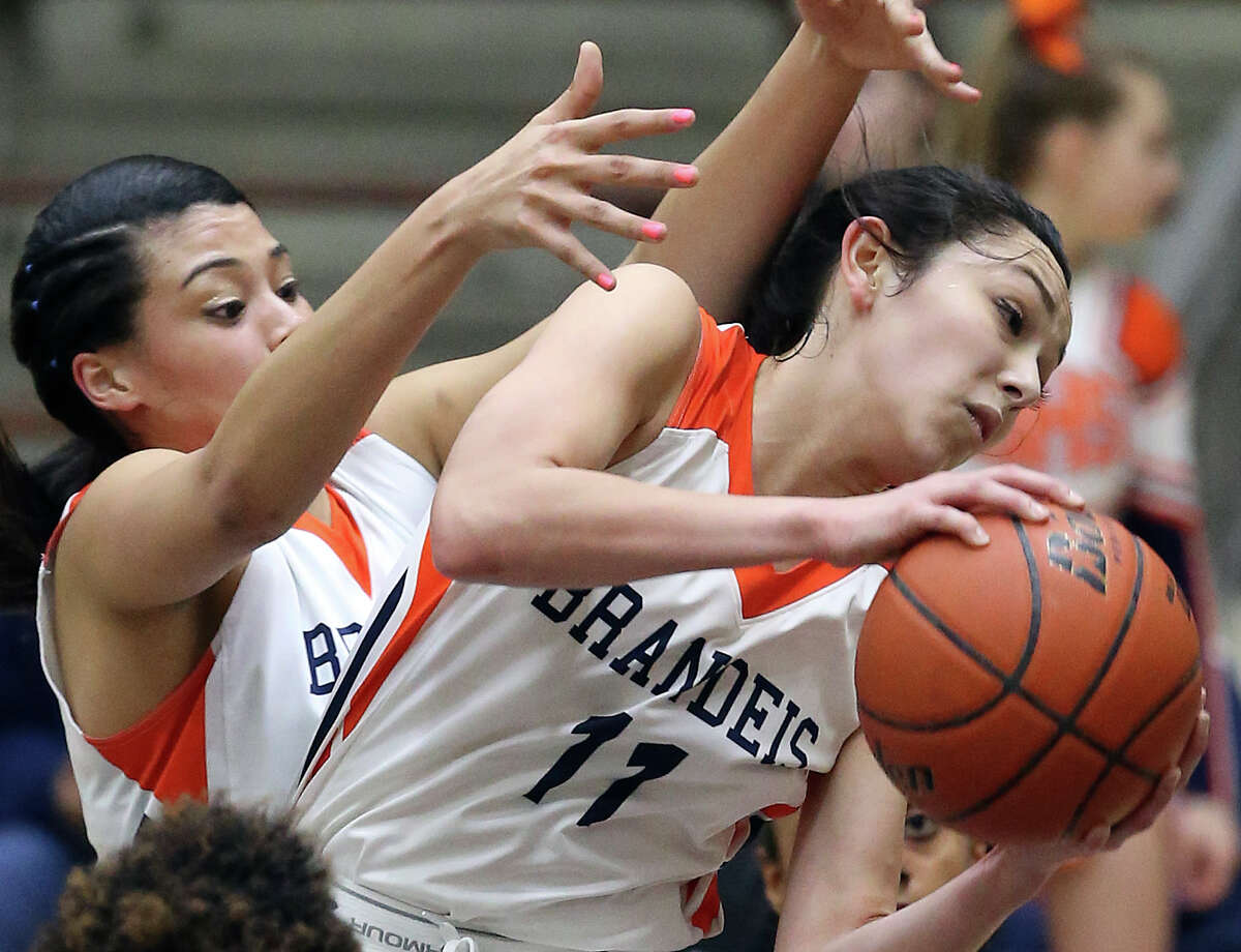 Bronco guard Kyana Alvarez rips a rebound down under the protection of teammate Morgan Williams as Brandeis plays Wagner in second round 6A girls basketball playoff action at the Alamo Convocation Center on February 20, 2015