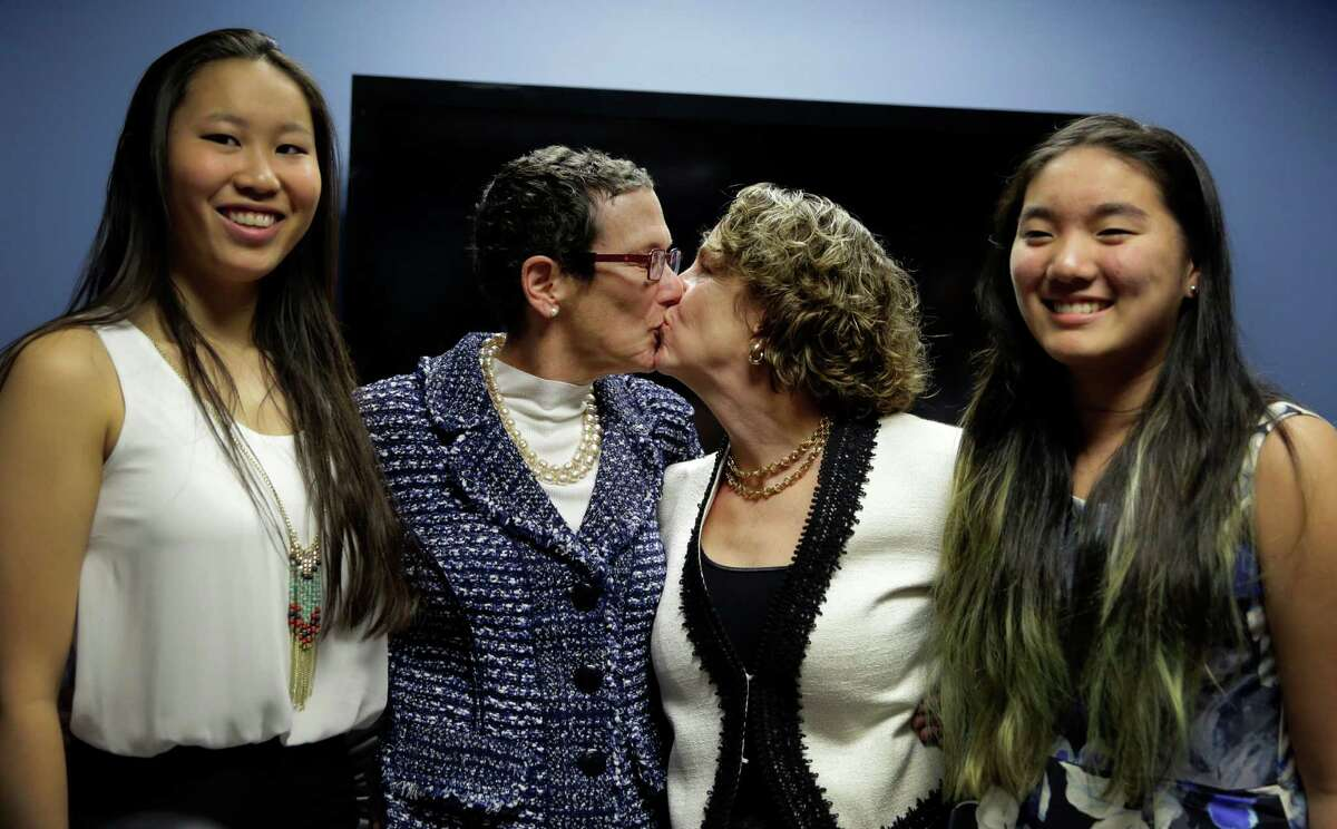 Sarah Goodfriend, left center, and Suzanne Bryant, right center, share a kiss as they pose with their daughters, Dawn Goodfriend, left and Ting Goodfriend, right, following a news conference, Thursday, Feb. 19, 2015, in Austin, Texas. Despite Texas' longstanding ban on gay marriage, the same-sex couple married Thursday immediately after being granted a marriage license under a one-time court order issued for medical reasons. (AP Photo/Eric Gay)