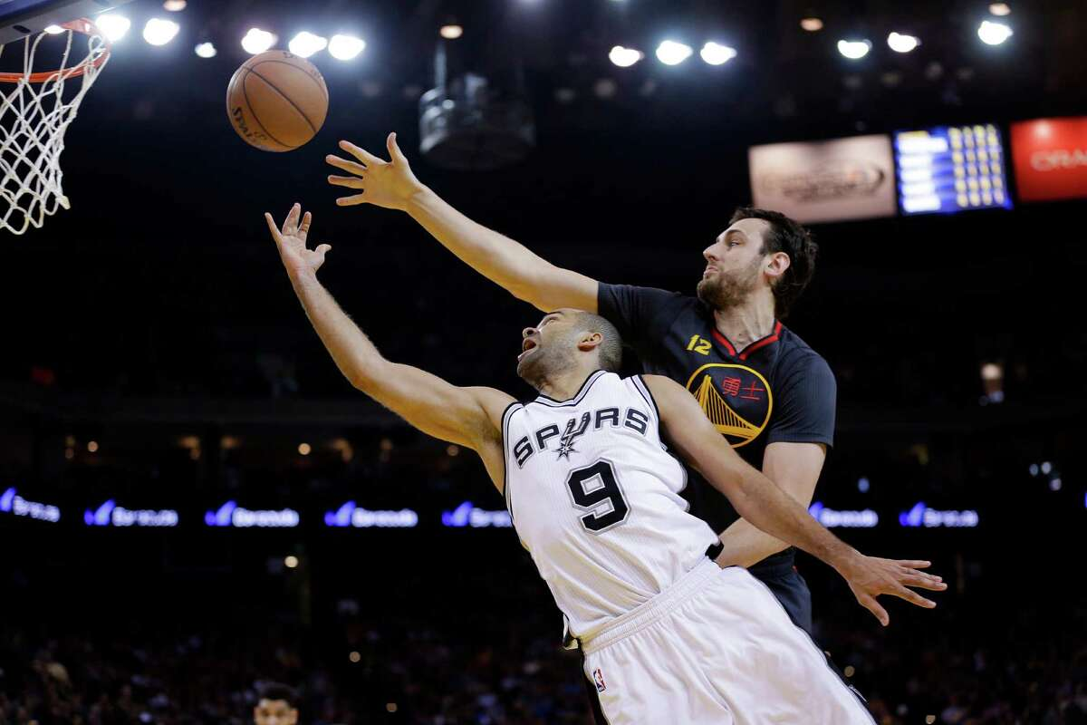 San Antonio Spurs' Tony Parker (9) scores past Golden State Warriors' Andrew Bogut during the first half of an NBA basketball game Friday, Feb. 20, 2015, in Oakland, Calif. (AP Photo/Marcio Jose Sanchez)