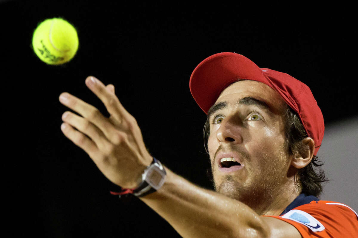 Pablo Cuevas of Uruguay, serves to Rafael Nadal of Spain at the quarter-finals of the Rio Open tennis tournament in Rio de Janeiro, Brazil, early Saturday, Feb. 21, 2015.
