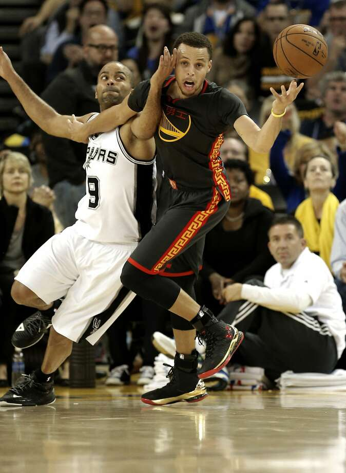 Spurs' Tony Parker, 9 and Warriors' Stephen Curry, 30 battle for a ball during the first half, as the Golden State Warriors take on the San Antonio Spurs in NBA action at Oracle Arena in Oakland, Calif. on Fri. Feb. 20, 2015. Photo: Michael Macor, The Chronicle
