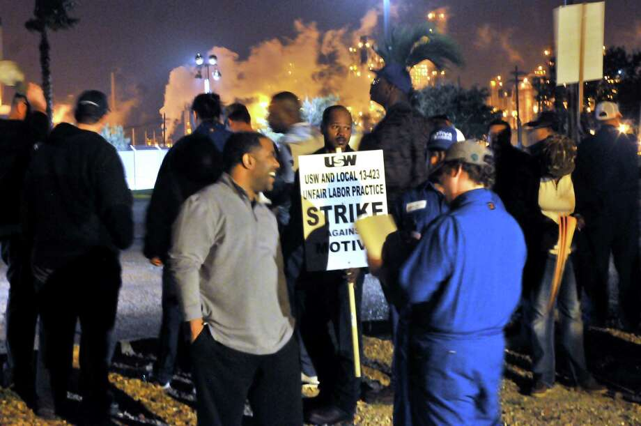The glow of the Motiva Port Arthur refinery lights illuminates the view across Savannah Avenue as member of the United Steelworkers and Local 13-423 strike just after midnight on Saturday, Feb. 21, 2015. Union member Steven Wilkerson, center, holds a picket sign as fellow co-workers gather at the corner of Savannah Avenue. Photo: Mike Tobias