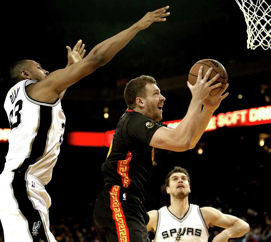 Warriors' David Lee (10) drives between Boris Diaw (left) and Tiago Splitter during the first half. The Warriors went on a 17-2 run spanning the second and third quarters to take control of the game. Photo: Michael Macor / The Chronicle / ONLINE_YES