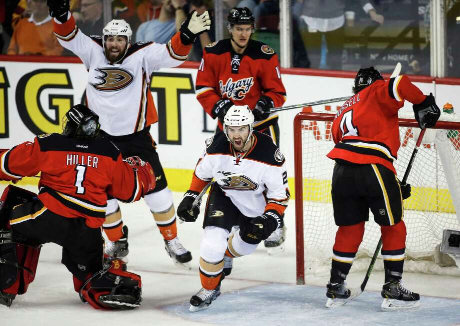 Kyle Palmieri (center) celebrates his goal while Ducks teammate Patrick Maroon (second from left) cheers and Calgary Flames goalie Jonas Hiller (left) watches in the third period. Photo: Jeff McIntosh / Associated Press / The Canadian Press