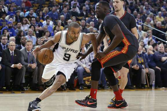 San Antonio Spurs' Tony Parker (9) dribbles past Golden State Warriors' Draymond Green, center, and Klay Thompson during the first half of an NBA basketball game Friday, Feb. 20, 2015, in Oakland, Calif.